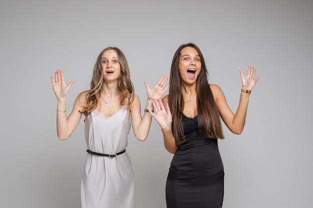 Twee mooie vrouwen die in de studio staan en hun vingers naar boven wijzen, geïsoleerd op een grijze achtergrond