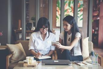 Twee mooie vrouwen die in een koffiewinkel werken