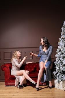 Twee mooie vrouwen die kerstmis samen met manierkleding vieren. kerst thuis