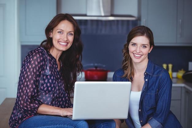 Twee mooie vrouwen die laptop in keuken met behulp van
