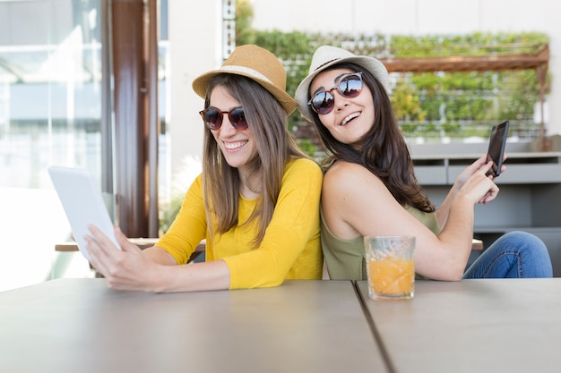 Twee mooie vrouwen die ontbijt in een restaurant hebben. ze lachen en zoeken informatie op een tablet. binnenshuis levensstijl en vriendschapsconcept