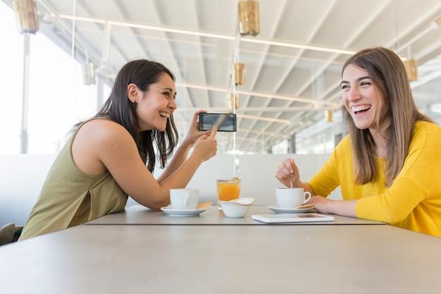 Twee mooie vrouwen die ontbijt in een restaurant hebben. ze lachen en zoeken informatie op hun mobiele telefoon. binnenshuis levensstijl en vriendschapsconcept