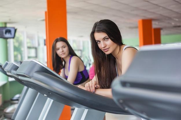 Twee mooie vrouwen die op de tredmolen in de gymnastiek lopen. mooie meisjes op de renbaan die binnen en opleiden glimlachen
