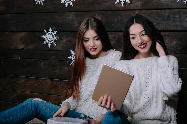 Twee mooie vrouwen die op de vloer zitten met een tablet