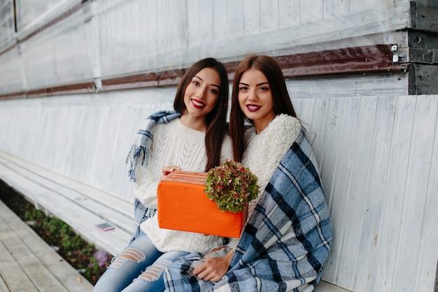 Twee mooie vrouwen die op een bank zitten en in hun handengift houden