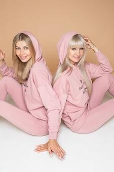 Twee mooie vrouwen die roze sweatshirts en beenkappen dragen die rug aan rug zitten en glimlachen