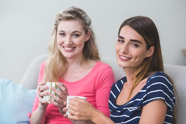Twee mooie vrouwen die zij aan zij met een mok koffie zitten
