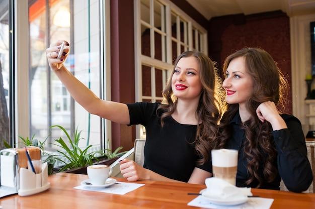 Twee mooie vrouwen doen selfie en drinken koffie