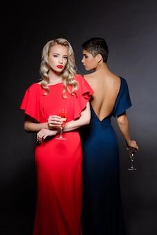 Twee mooie vrouwen in avondjurken poseren, champagne glas te houden