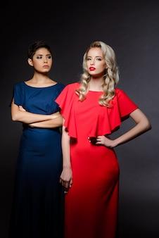Twee mooie vrouwen in avondjurken poseren