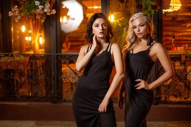 Twee mooie vrouwen in de avond op straat het stellen, feestelijke stemming.