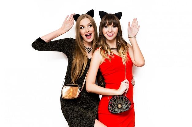 Twee mooie vrouwen in de oren van kattencarnaval en avondjurk die pret hebben
