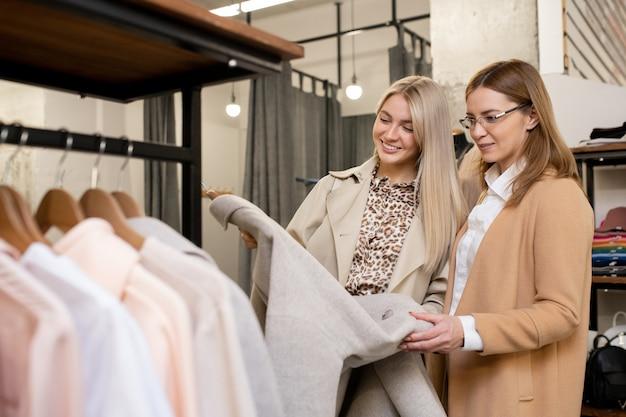 Twee mooie vrouwen in nette vrijetijdskleding kijken naar een elegante lichtgrijze jas terwijl ze er op hun gemak een uitkiezen in een moderne boetiek
