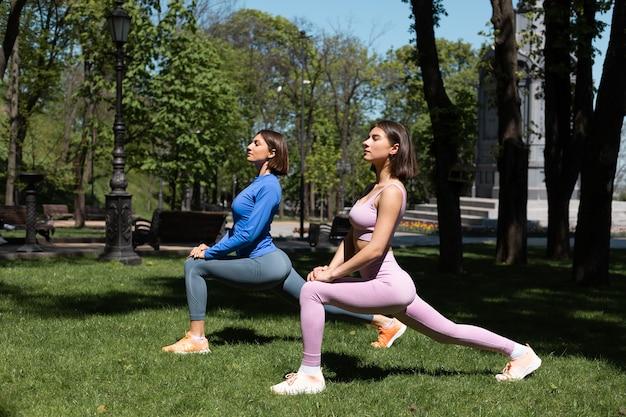 Twee mooie vrouwen in sportkleding op gras in park op zonnige dag doen yoga houdingen, zonnestralen vangen