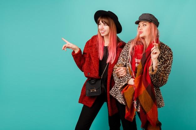 Twee mooie vrouwen in stijlvolle faux fur jassen en wollen sjaal poseren op turquoise muur