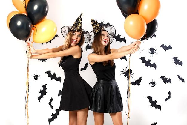Twee mooie vrouwen in zwarte jurken en heksenhoeden hebben plezier met zwarte en oranje ballonnen. halloween feest .