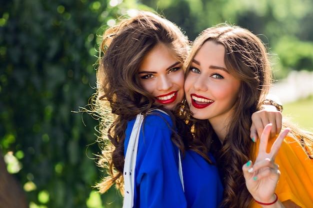Twee mooie vrouwen knuffelen en glimlachen