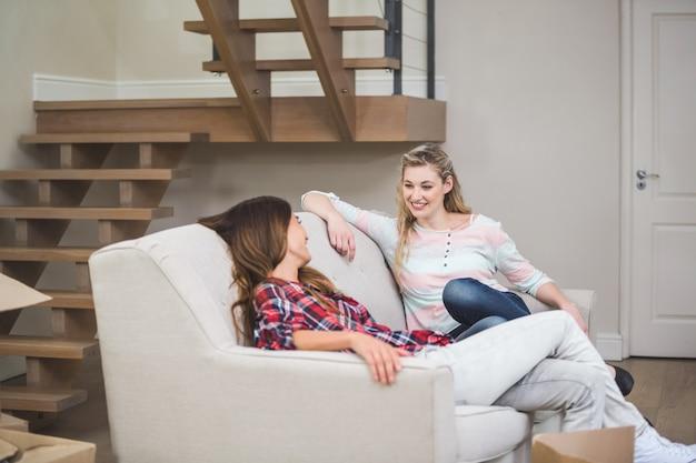 Twee mooie vrouwen met elkaar praten terwijl u ontspant op de bank