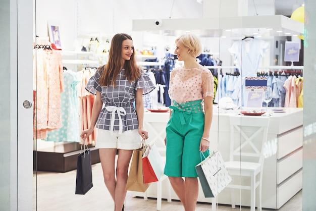 Twee mooie vrouwen met tassen kijken elkaar met een glimlach tijdens het wandelen in de kledingwinkel