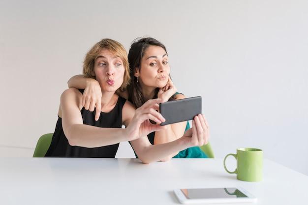 Twee mooie vrouwen op kantoor die een selfie met mobiele telefoon nemen. witte achtergrond. modern kantoorconcept