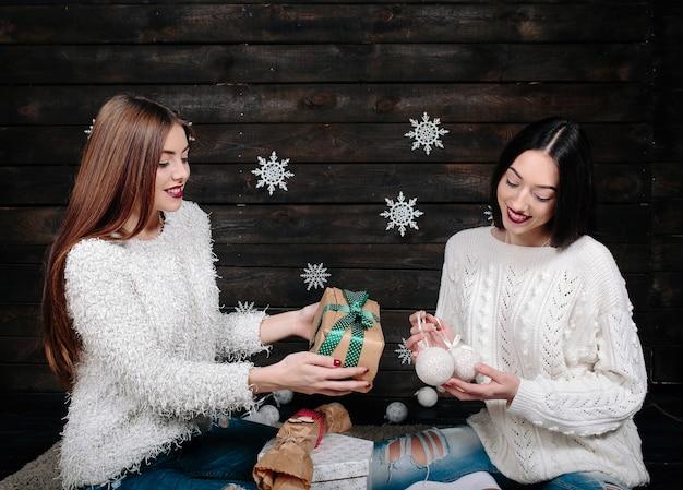 Twee mooie vrouwen poseren met cadeaus voor kerstmis