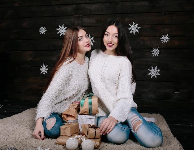 Twee mooie vrouwen poseren met geschenken voor kerstmis, dichtbij bekeken
