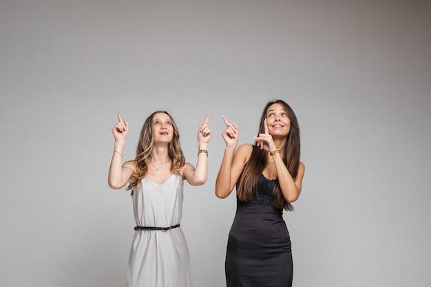 Twee mooie vrouwen staan in de studio met hun vingers omhoog, op grijs .. kopieer de ruimte