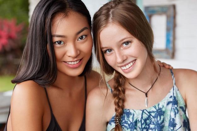 Twee mooie vrouwen van verschillende nationaliteiten hebben echte vriendschap, ontmoeten elkaar na lange tijd, blij elkaar te zien.