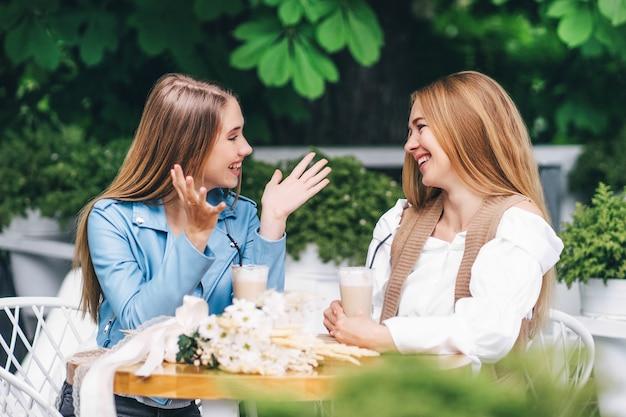 Twee mooie vrouwen zitten aan een tafel in een coffeeshop en communiceren emotioneel en glimlachen naar elkaar