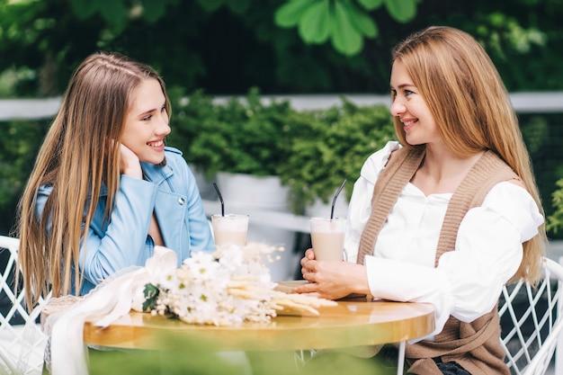 Twee mooie vrouwen zitten aan een tafel in een coffeeshop en communiceren emotioneel