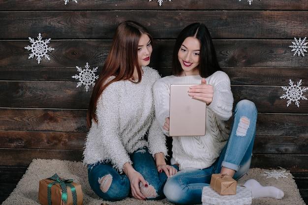 Twee mooie vrouwen zittend op de vloer met een tablet, tussen cadeaus voor kerstmis
