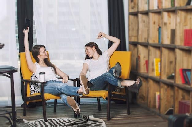 Twee mooie vrouwenvrienden die gelukkige glimlach onder de boeken thuis spreken