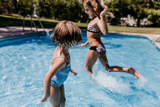 Twee mooie zus kinderen bij het zwembad spelen, rennen en plezier buitenshuis. zomer en levensstijl concept