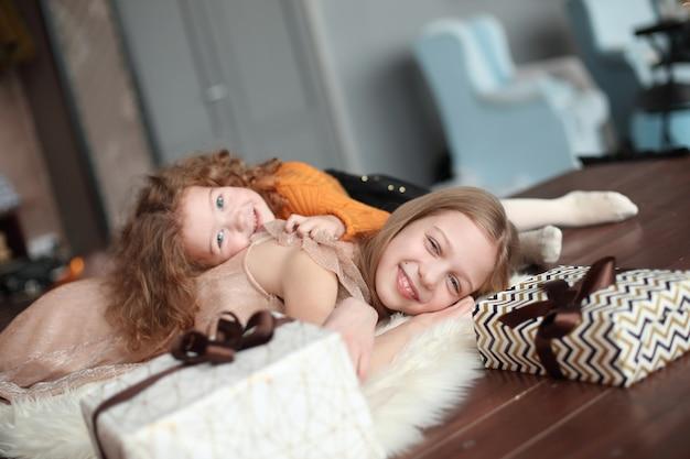 Twee mooie zussen die op de vloer liggen in een gezellige woonkamer.