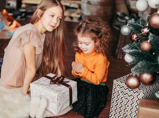 Twee mooie zussen met cadeautjes zittend op de vloer op kerstavond. vakantie concept