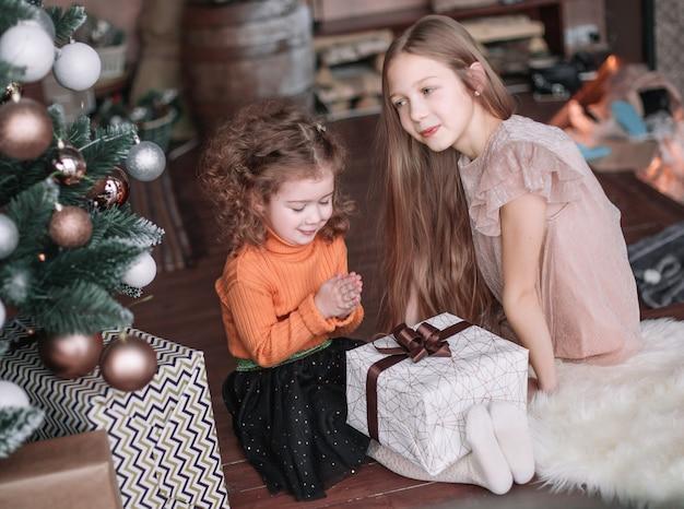 Twee mooie zussen met cadeautjes zittend op de vloer op kerstavond.