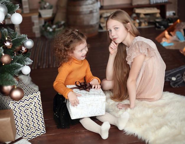 Twee mooie zussen openen een doos met geschenken. het concept van kerstmis