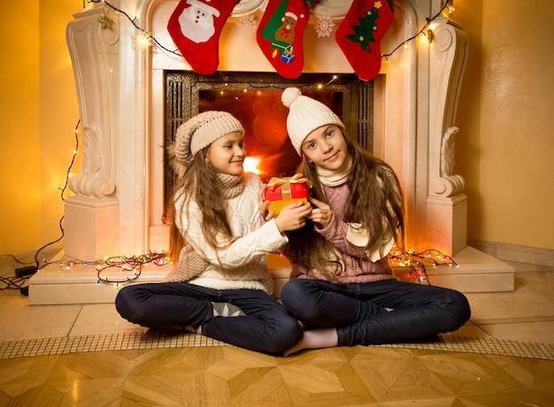 Twee mooie zussen zitten naast de open haard met kerstcadeaus