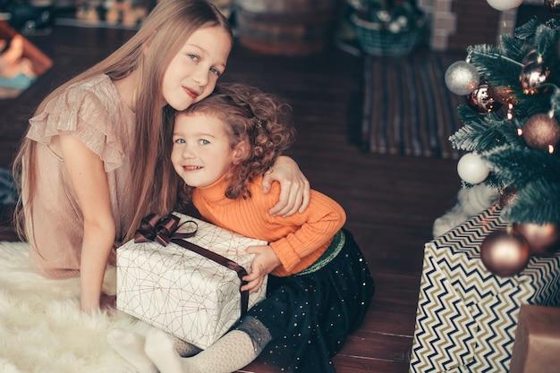 Twee mooie zussen zittend op de vloer op kerstavond. vakantie concept