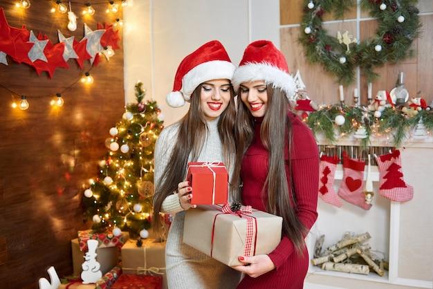Twee mooie zusters die santa claus-hoeden dragen die kerstmis vieren