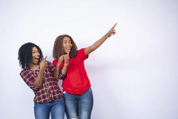 Twee mooie zwarte vrouw wijzend op iets blij en opgewonden