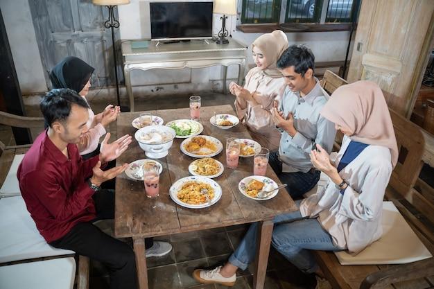 Twee moslimmannen en drie gesluierde vrouwen bidden samen voor het eten