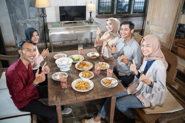 Twee moslimmannen en drie vrouwen in sluier glimlachend met duimen omhoog