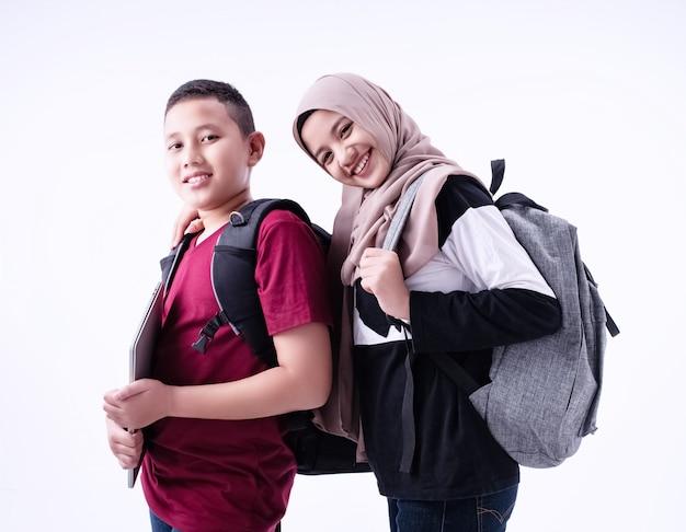 Twee moslimstudenten die zich samen, op witte achtergrond bevinden, met glimlach en gelukkig gevoel