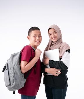 Twee moslimstudenten staan samen, op witte achtergrondkleur, met een glimlach en gelukkig gevoel, zus en broer, klaar om naar school te gaan