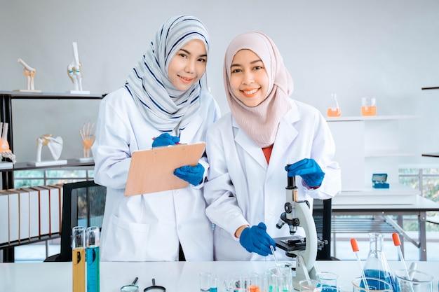 Twee moslimvrouwen chemische wetenschapper die het experiment in laboratorium doen.