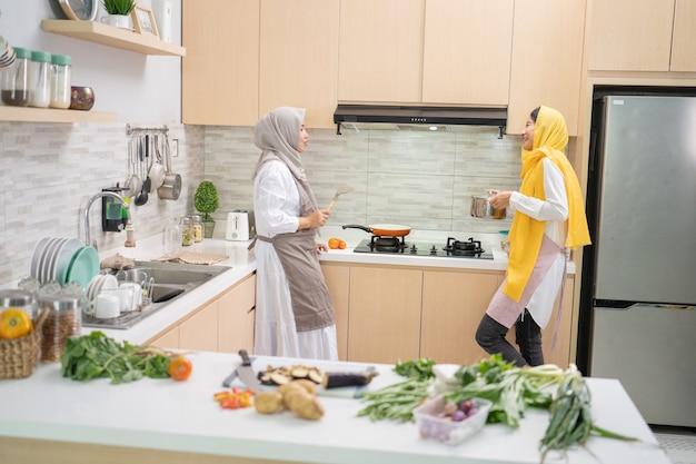 Twee moslimvrouwen die plezier hebben tijdens het samen koken in de keuken