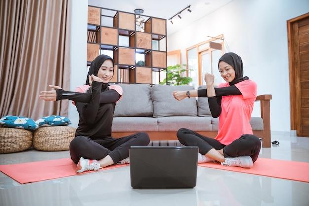 Twee moslimvrouwen in sportkleding zitten aan het opwarmen met een hand die de andere hand vasthoudt wanneer een hand opzij wordt getrokken terwijl ze thuis gezamenlijke activiteiten doen