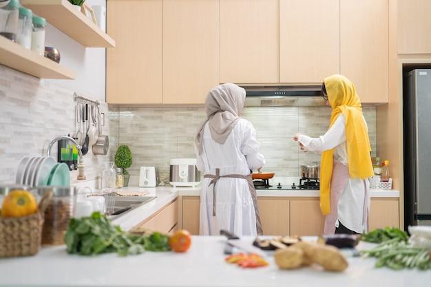 Twee moslimvrouwen plezier tijdens het koken samen in de keuken