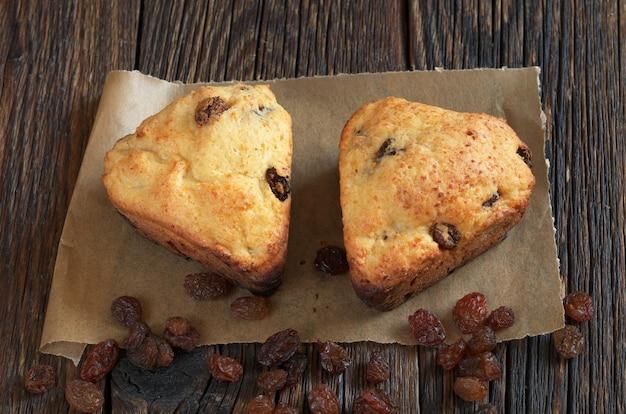 Twee muffins met rozijnen in de vorm van harten op oude houten tafel